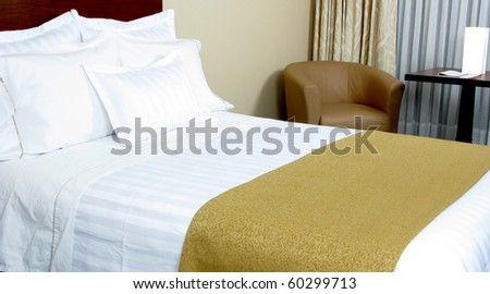 Image of comfortable suite with pillows and bed.