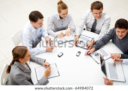 Image of company of successful partners looking at their colleague at meeting