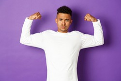 Image of confident african-american young guy, flexing biceps and trying to show-off, showing muscles after workout, standing over purple background, feeling strong