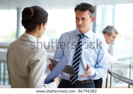 Image of confident businessman looking at partner while discussing new strategy