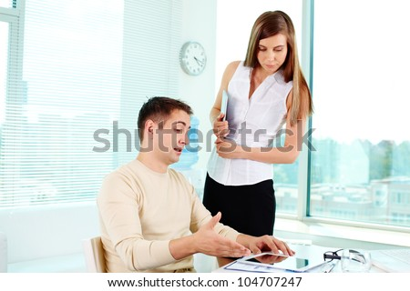 Image of confident businessman pointing at tablet with pretty colleague near by