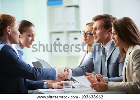 Image of confident businessmen handshaking at meeting - stock photo