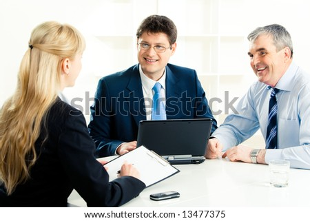 Image of confident businessmen looking at young secretary during meeting while discussing their work