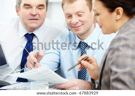 Image of confident colleagues discussing papers at meeting