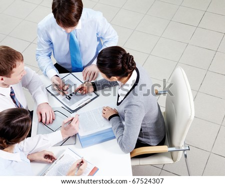 Image of confident employees discussing papers at meeting