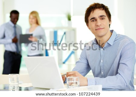 Image of confident leader with laptop looking at camera from workplace