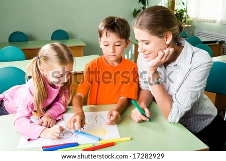 Image of confident teacher looking at girlâ??s picture with cute boy near by