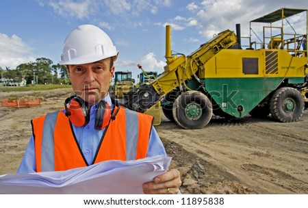 Image of construction manager or engineer at roadworks surveying plans