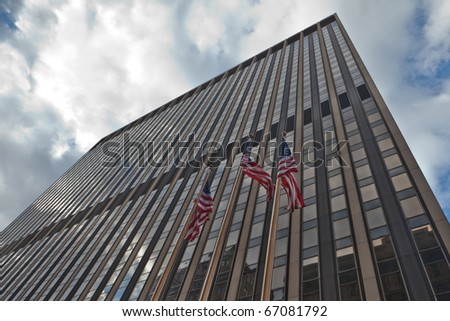 Image of corporate America: Skyscraper with American flags waving in New York city.