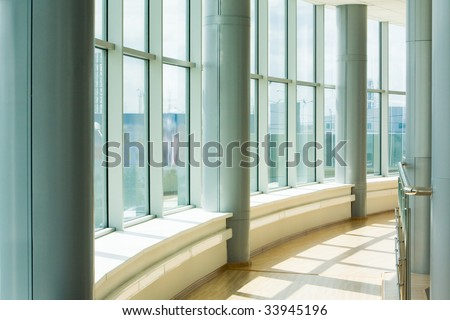 Image of corridor in office building with big windows passing daylight
