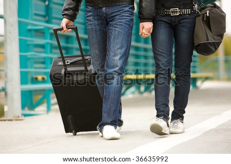Image of couple walking down train station with their baggage