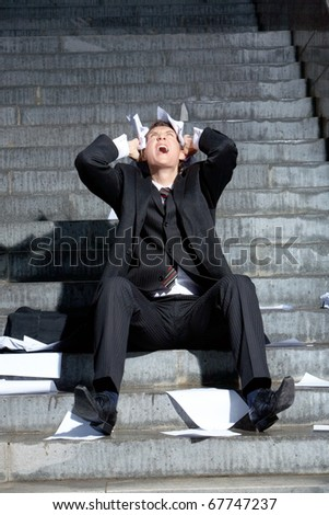 Image of crying businessman with papers in hands touching his head