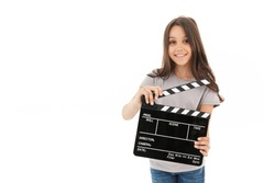 Image of cute girl standing isolated over white wall background holding film making clapperboard.