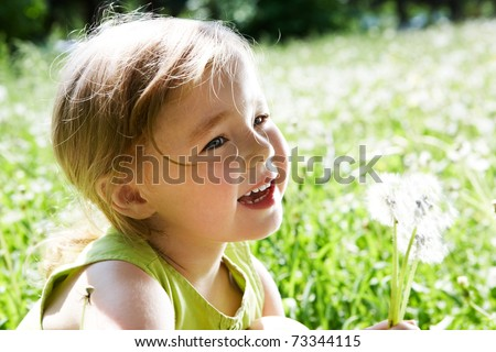 Image of cute girl with white dandelions on background of green grass