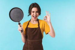 Image of cute happy young woman chef holding frying pan isolated over blue wall background showing okay gesture.