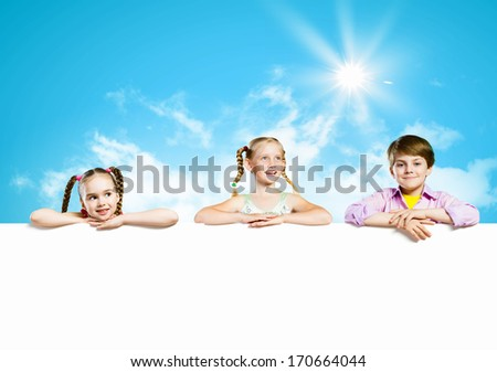 Image of cute kids holding blank white banner. Place for text