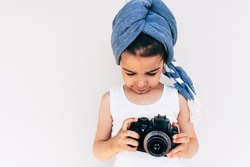 Image of cute little girl wearing turban on the head holding an photo camera, isolated on white background. Adorable child taking a picture with a professional camera posing on white background.