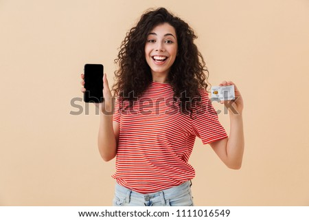 Image of cute pretty young curly woman isolated over beige background showing display of mobile phone holding credit card.