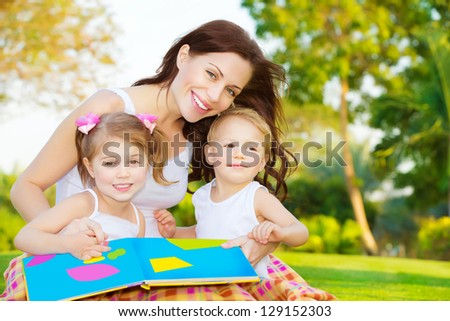 Image of cute young female with two little children read book outdoors, cheerful mother and two pretty kids sitting down on  backyard and enjoying spring nature, daycare, loving family concept - stock photo