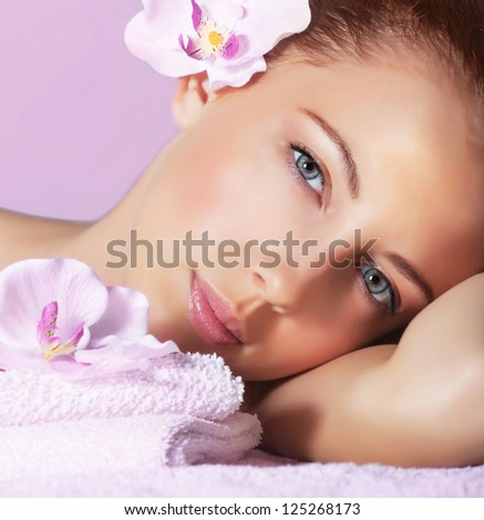 Image of cute young lady enjoying dayspa, closeup portrait of pretty woman with orchid flower in head on pink background, luxury spa resort, healthy lifestyle, beauty treatment and skin care concept