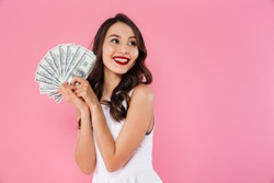 Image of delighted asian woman 20s holding fan of money in dollar cash and looking aside on copyspace with smile isolated over pink background