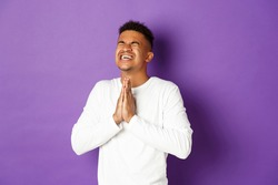 Image of desperate african-american guy pleading to God, holding hands in pray and begging for something, making wish, standing worried over purple background