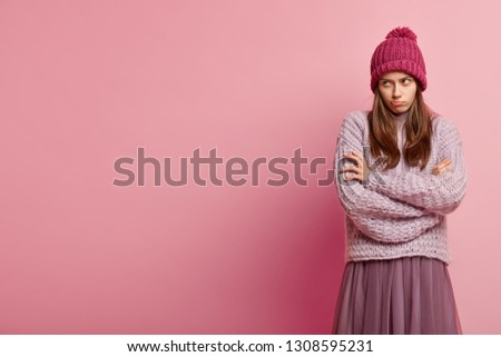 Image of discontent woman with angry dissatisfied facial expression, keeps hands crossed, looks offensively, dressed in winter outfit, isolated over pink background with free space for your text