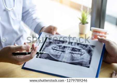 Image of doctor or dentist presenting with tooth x-ray film recommend patient in the treatment of dental and dentistry, working at workplace.