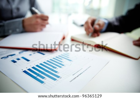 Image of document with charts on background of male and female hands with pens over open notebooks at seminar