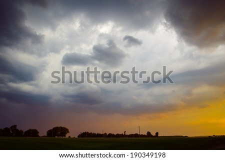 image of dramatic thunder storm clouds at sunset landscape