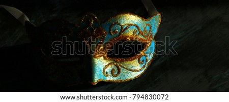 Image of elegant blue and gold venetian, mardi gras mask over black background #794830072