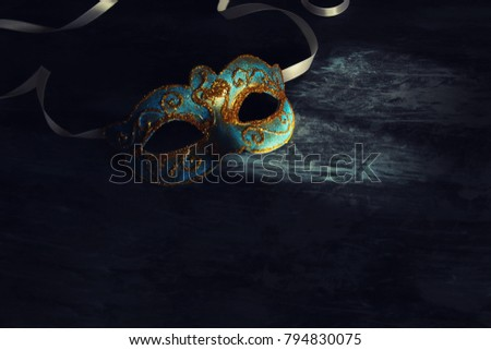 Image of elegant blue and gold venetian, mardi gras mask over black background #794830075