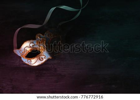 Image of elegant blue and gold venetian, mardi gras mask over dark background. Vintage filtered photo #776772916