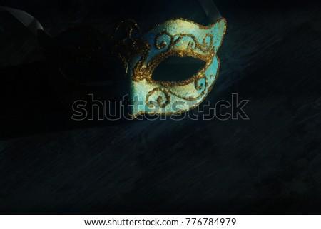 Image of elegant blue and gold venetian, mardi gras mask over dark background. Vintage filtered photo #776784979
