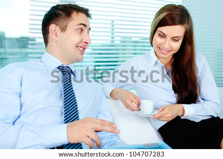 Image of elegant businessman sharing his idea with pretty colleague at meeting