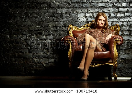 Image of elegant girl sitting in retro style armchair and looking at camera