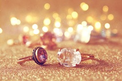 Image of elegant gold rings on gold glitter background