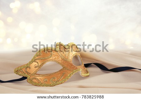Image of elegant gold venetian mask over delicate silk fabric background #783825988