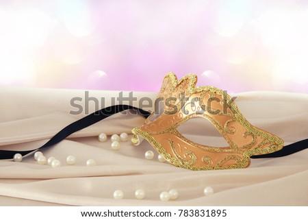 Image of elegant gold venetian mask over delicate silk fabric background #783831895