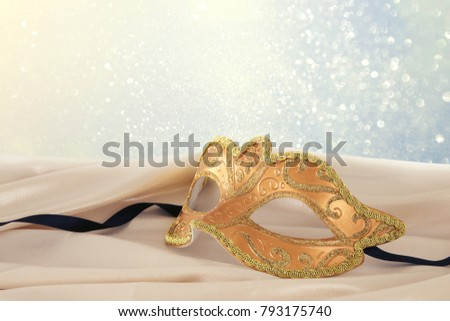 Image of elegant gold venetian mask over delicate silk fabric background #793175740