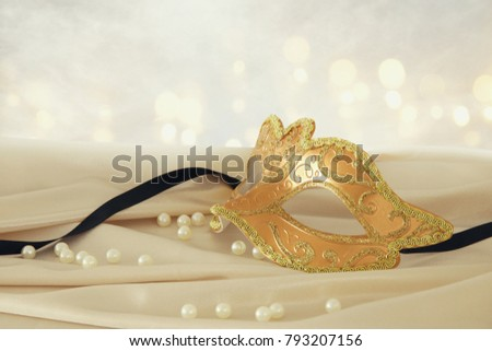 Image of elegant gold venetian mask over delicate silk fabric background #793207156