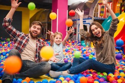 Image of emotional cheerful little child have fun with his parents in entertainment game center.
