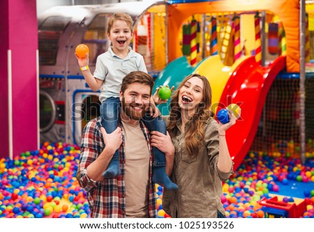 Image of emotional cheerful little child have fun with his parents in entertainment game center. #1025193526
