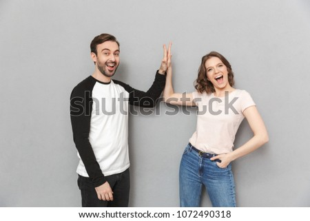 Image of emotional couple friends standing isolated over grey wall background gives a high five to each other.