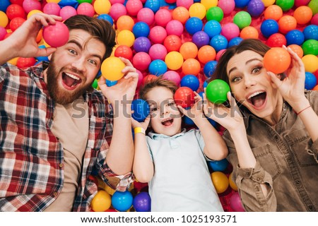 Image of emotional little child have fun with his parents in entertainment game center. Looking camera.