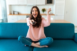 Image of emotional smiling optimistic young woman sit indoors at home watch tv holding remote control on sofa make winer gesture.