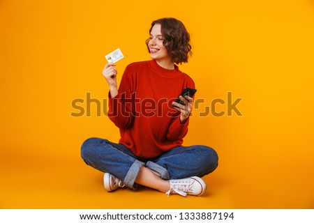 Image of emotional young pretty woman posing isolated over yellow wall background using mobile phone holding credit card.