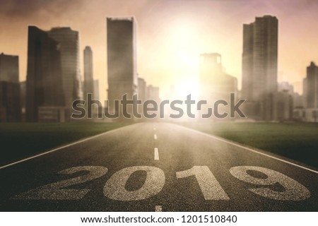 Image of empty roadway with number 2019 toward modern city at sunrise time