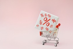 Image of empty shopping trolley or cart with box of discount percent sale black Friday products on pink background. Concept of sell or buy with place for your text