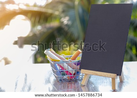 Image of empty small chalkboard on wooden easel and colorful chalk sticks in basket over wooden table outdoor with blurred nature background. Mock-up of menu blackboard. Blank blackboard display label #1457886734